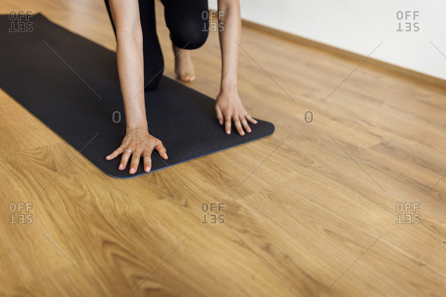 Low section of woman placing exercise mat on hardwood floor in yoga studio