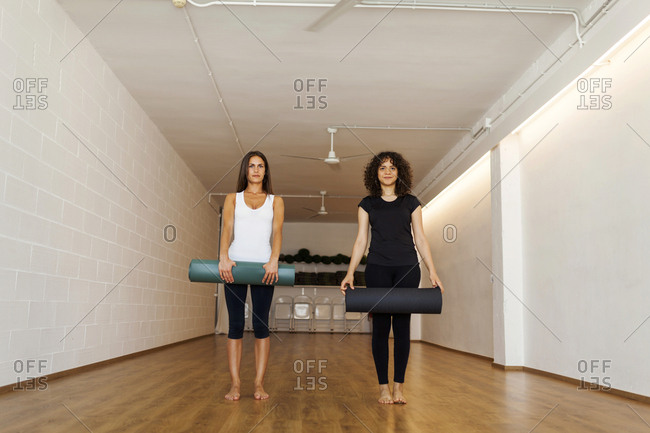 Portrait of female friends placing exercise mats on hardwood floor in yoga studio