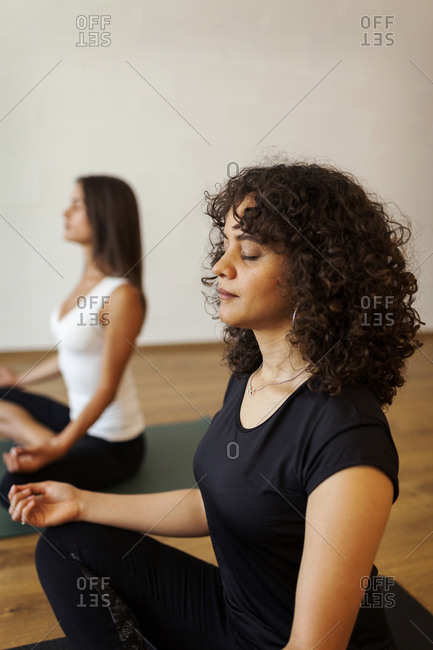 Female friends meditating in yoga studio