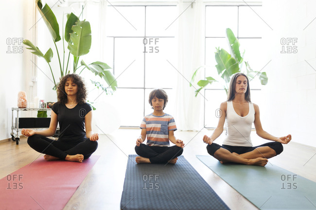 Female instructor with mother and son meditating against window in yoga studio