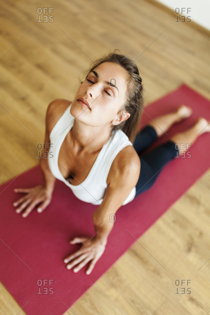 High angle view of woman with eyes closed practicing cobra pose in yoga studio