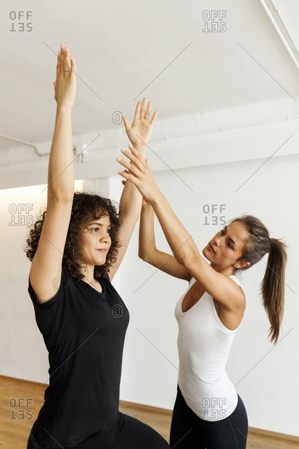 Yoga instructor guiding woman exercising in yoga studio