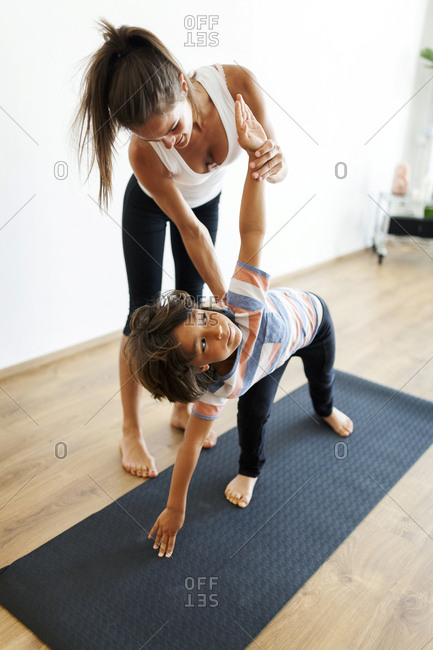 Yoga instructor assisting boy in exercising at yoga studio