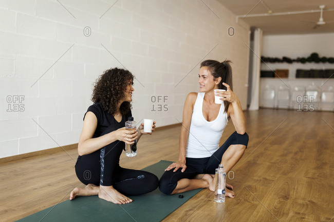 Female friends talking while having drinks in yoga class