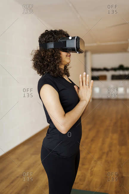 Side view of woman wearing virtual reality simulator while meditating in yoga class
