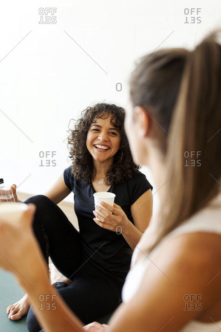 Female friends talking while having water in yoga class