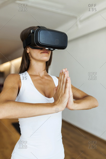 Woman wearing virtual reality simulator while meditating in yoga studio