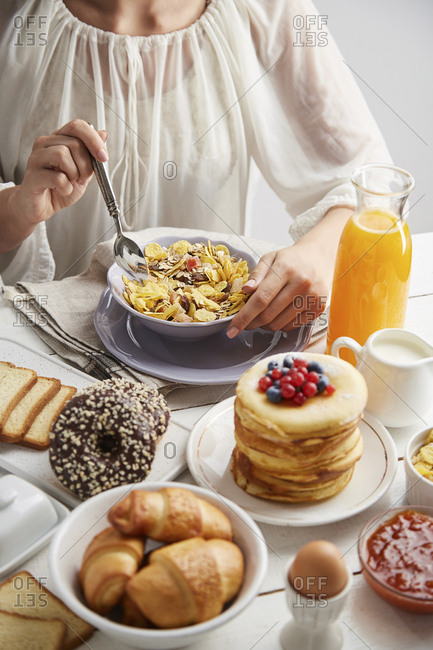 Midsection of woman having breakfast on table at home