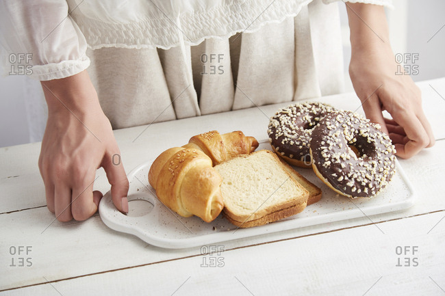 Midsection of woman holding donuts with bread and croissants in tray on table at home