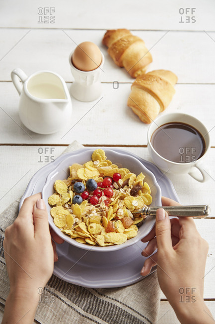 Cropped hands of woman holding bowl with breakfast cereals on table at home