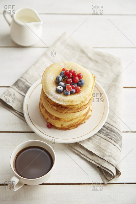 High angle view of pancakes served in plate with coffee and milk on wooden table
