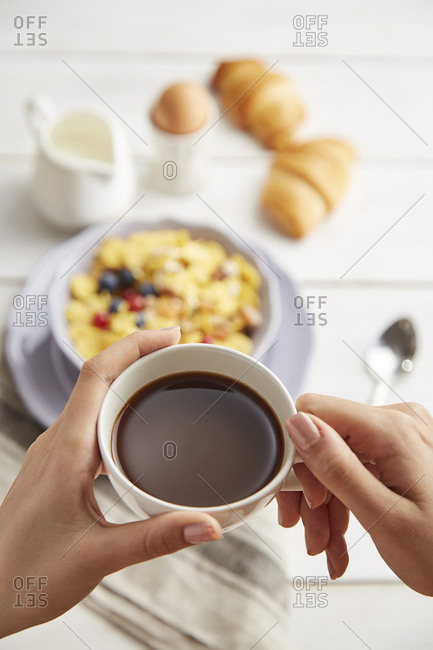 Cropped hands of woman holding coffee cup over table at home