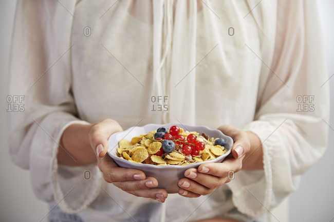 Midsection of woman having breakfast in bowl while standing at home