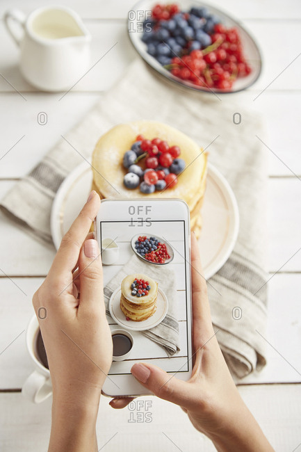 Cropped hands of woman photographing breakfast served on wooden table at home
