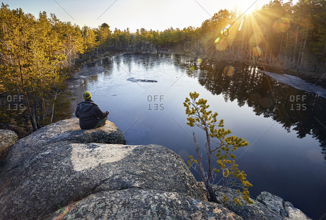 Rear view of man meditating while sitting on rock formation by lake in forest during sunrise