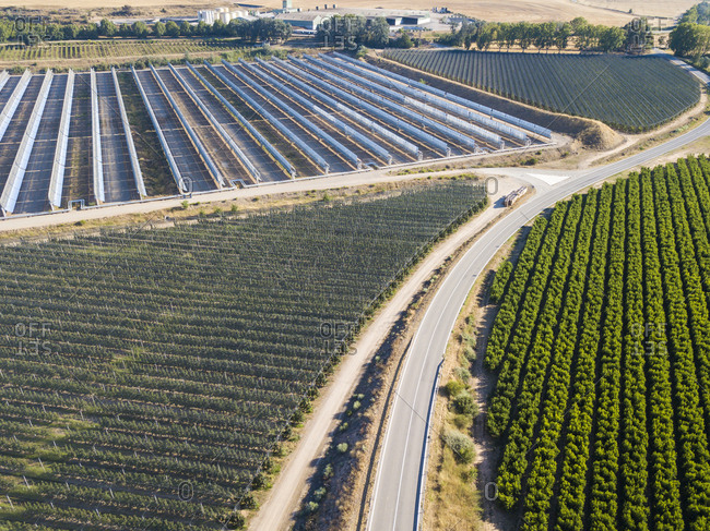 Aerial view of industrial infrastructure of solar cells, fields and high-speed railway tracks in Catalonia Spain