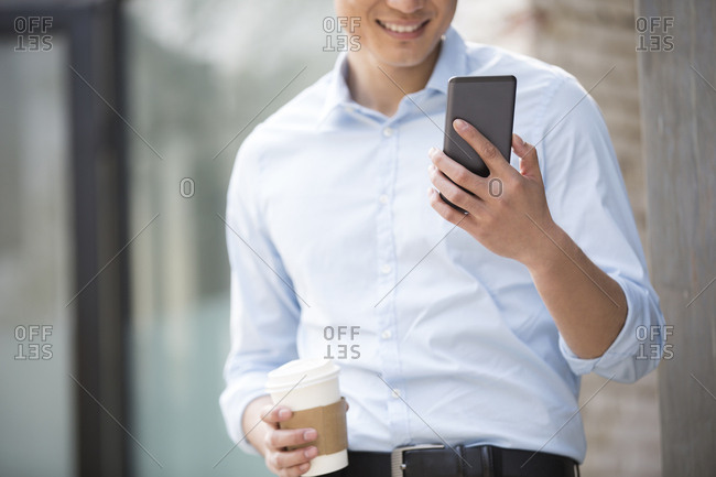 Young Chinese businessman with smart phone and coffee
