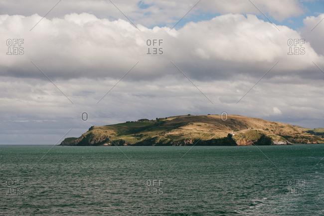 Distant lighthouse on coast of Dunedin, New Zealand