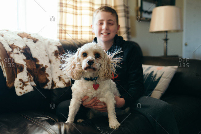 Boy holding white dog
