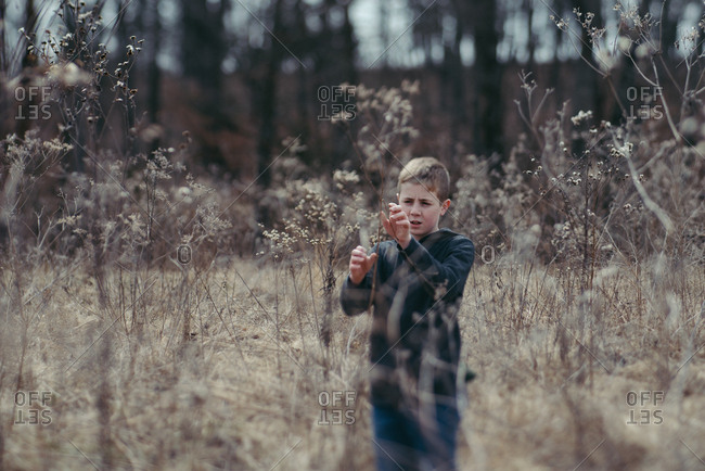 Boy exploring rural field in late winter
