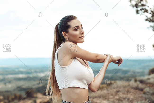 Young woman with long hair stretching her arm before workout