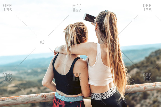 Rear view of young women taking selfie during workout
