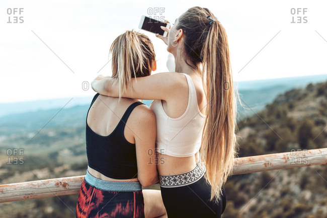 Back view of young women taking selfie during workout