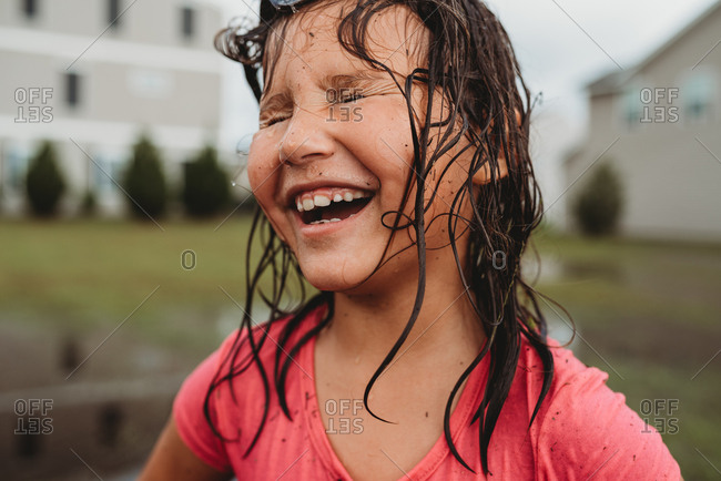 Portrait of a laughing girl with wet messy hair and dirty face playing in mud puddle