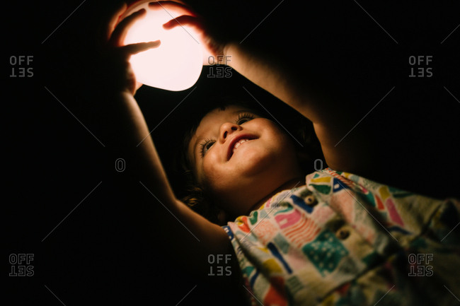 Baby girl playing with a light in the dark