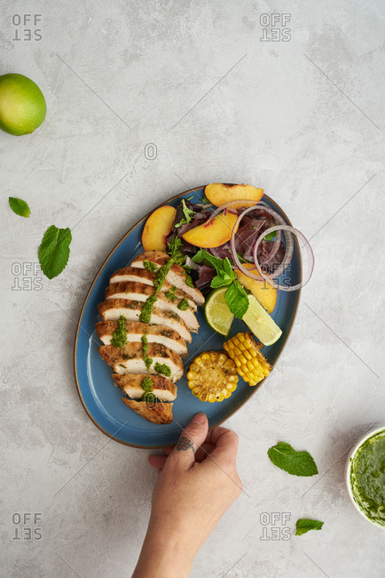 Grilled chicken summer salad with peaches and chimichurri sauce