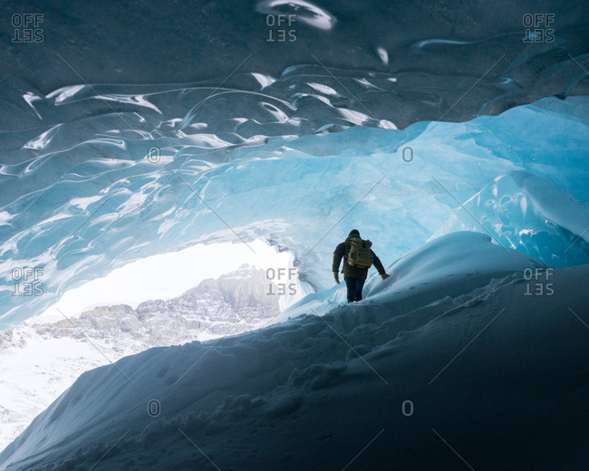 Person exploring inside of ice cave