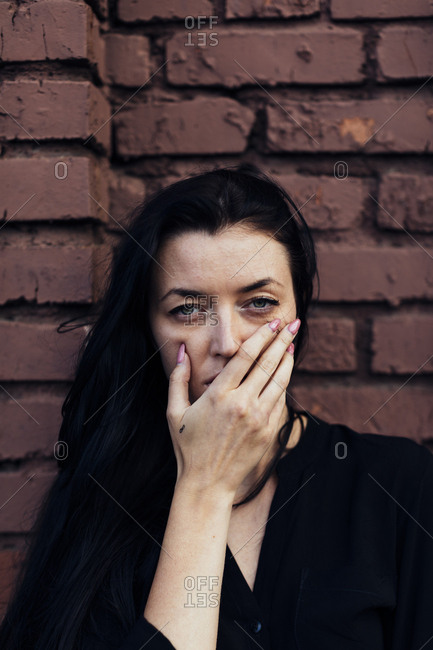 Woman with long dark hair covering her mouth in front of brick wall