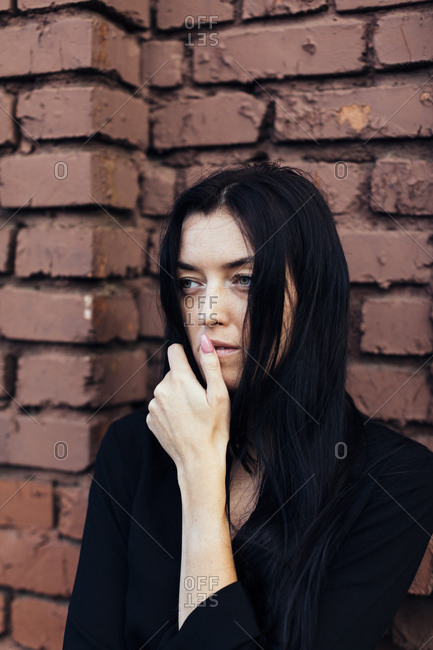 Woman with long dark hair touching her mouth in front of brick wall