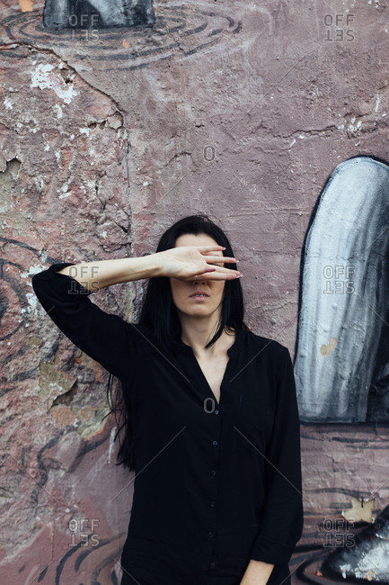 Woman with long dark hair covering her eyes