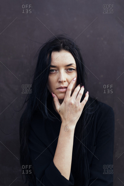 Woman with long dark hair in front of dark background