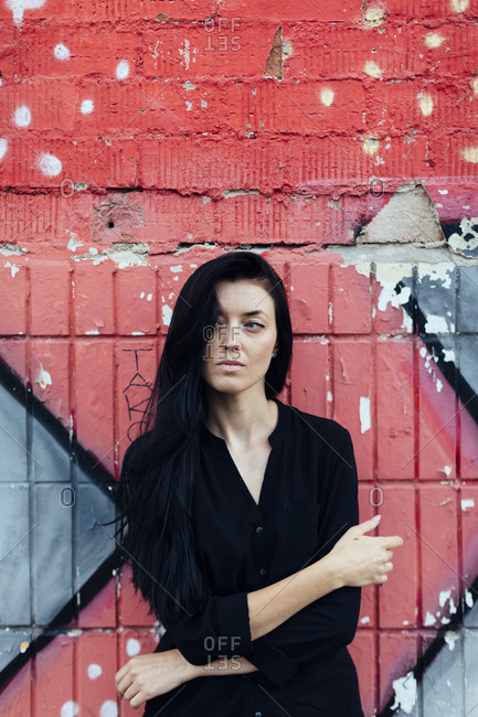 Woman with long dark hair in front of painted wall