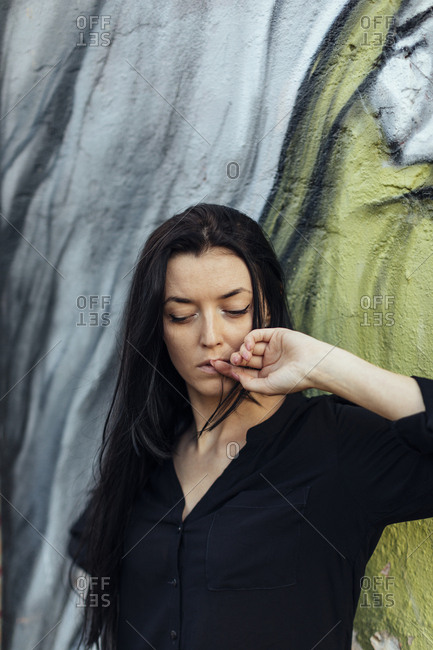 Woman with long dark hair in front of painted mural