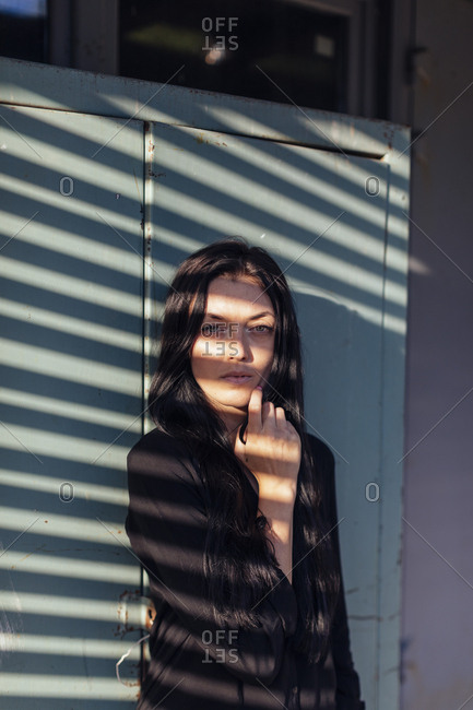 Woman with long dark hair with shadows covering her face