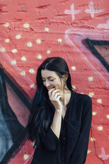 Smiling woman with long dark hair in front of red painted mural