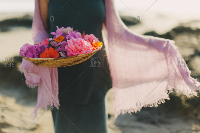 Woman holding colorful bowl of flowers