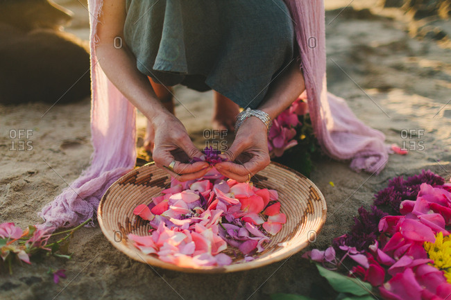 Woman placing colorful flower petals into a bowl