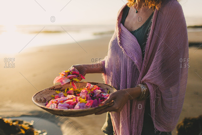Woman holding colorful bowl of flowers on a beach