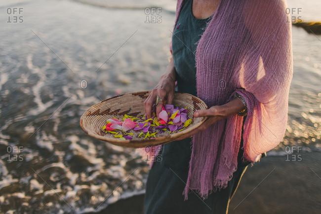 Woman with colorful bowl of flowers on a beach