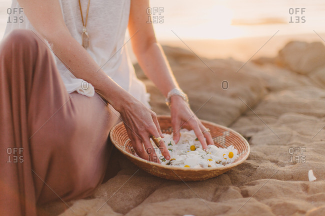 Woman sitting in sand beside bowl of daisies