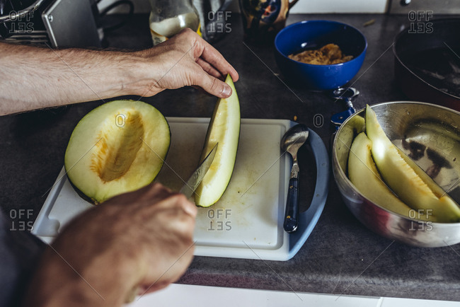 Man cutting melon on cutting board