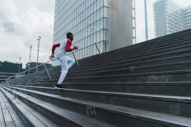 African-American sportsman running up stairs outdoors