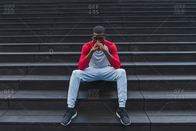 Handsome African-American resting man in sportswear sitting comfortably on grey wet stairs propping head with folded hands and looking at camera outdoors