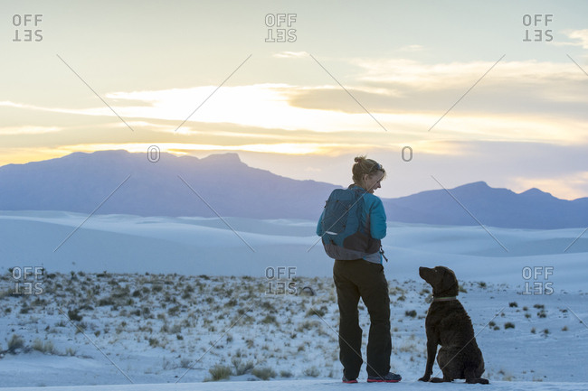 Woman and dog hiking in White Sands National Monument, Alamogordo, New Mexico, USA