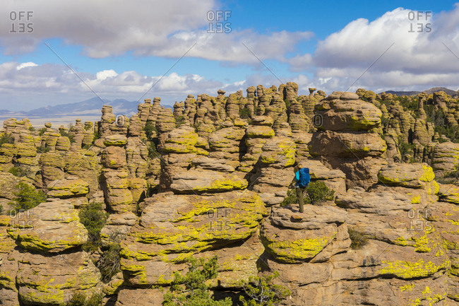 Distant view of woman hiking in Heart of Rocks, Chiricahua National Monument, Willcox, Arizona, USA