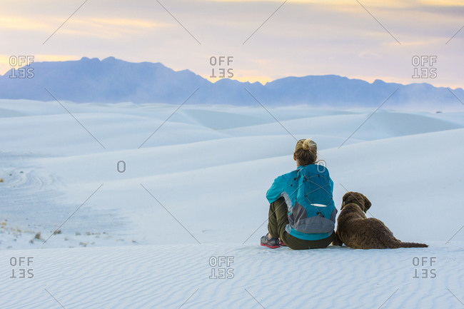 Rear view of woman and dog sitting while hiking in White Sands National Monument, Alamogordo, New Mexico, USA